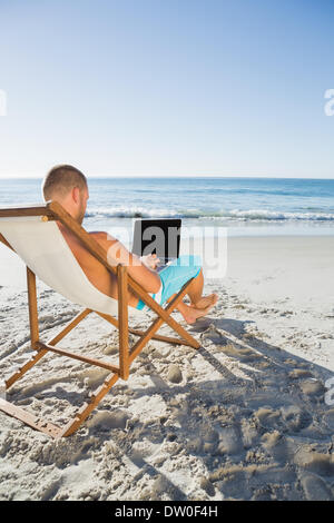 Focused handsome man working on his laptop - Stock Photo