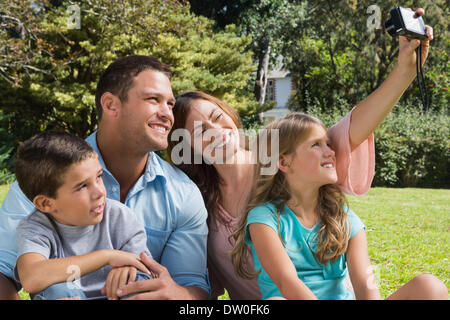 Happy family in a park taking photos - Stock Photo