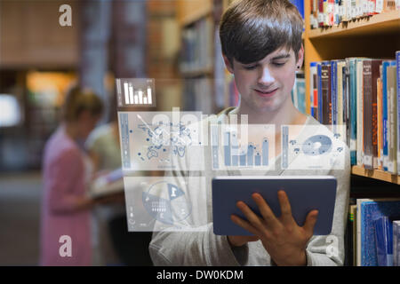 Young man studying on his futuristic tablet - Stock Photo