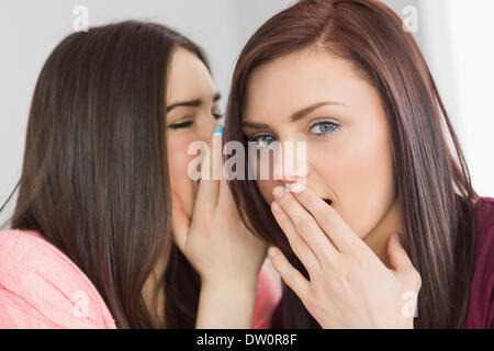 Two young girls sharing secrets - Stock Photo
