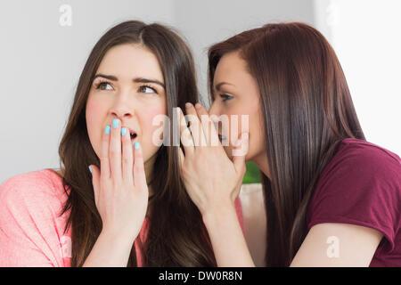 Two smiling girls sharing secrets - Stock Photo