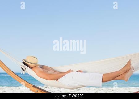 Man wearing straw hat relaxing in a hammock - Stock Photo