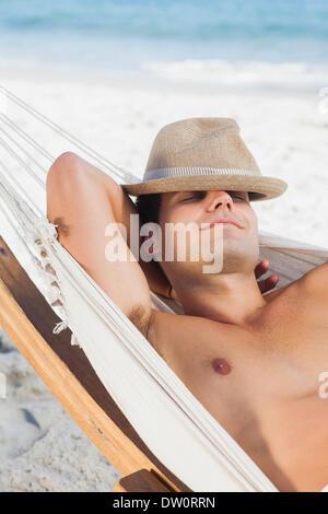 Man wearing straw hat lying in hammock - Stock Photo