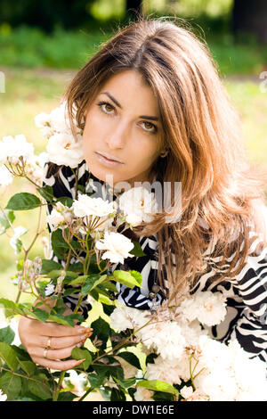 beautiful woman in garden with roses - Stock Photo