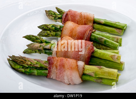 Fresh green asparagus wrapped in thick bacon. - Stock Photo