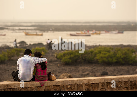 Couple relaxing on the Bandstand promenade in  Bandra, Mumbai, India waiting for the sunset. - Stock Photo