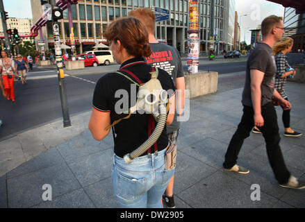 A German tourist carries a gas mask at Potsdamer Platz in Berlin, August 08, 2013. More and more tourists come to - Stock Photo