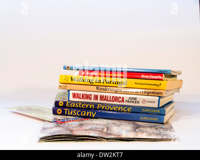Map and stack of books for hikes in different European countries, available in many languages - Stock Photo