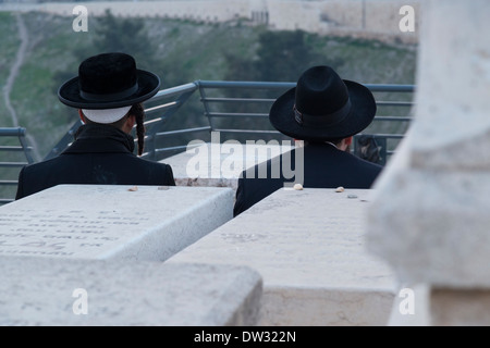 Orthodox Jews praying on a tomb at Mount of Olives cemetery. Jerusalem. Israel. - Stock Photo