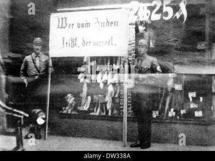Members of the SA (Sturmabteilung, the paramilitary wing of the Nazi party) stand in front of a Jewish shop holding - Stock Photo
