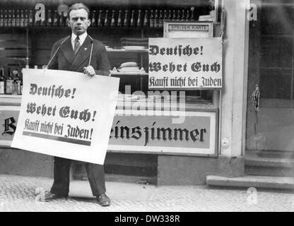 A man, who wears a poster around his neck reading 'Germans! Defend yourselves! Do not by from Jews!', stands in - Stock Photo