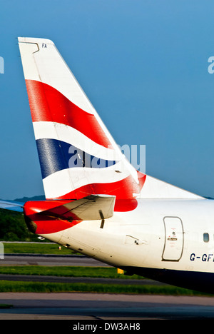 The tail fin of a British Airways jet taxiing at Manchester Airport, UK - Stock Photo