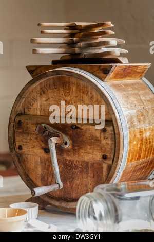 Antique butter churn with butter pats glass jar and ramekin in old farm house kitchen. - Stock Photo