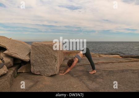 Iyengar Yoga Instructor Demonstrates Adho Mukha Vriksasana preparation (Inverted). - Stock Photo