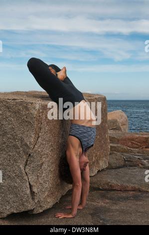 Iyengar ® Yoga Instructor Demonstrates Adho Mukha Vriksasana Padmasana (Inverted). - Stock Photo