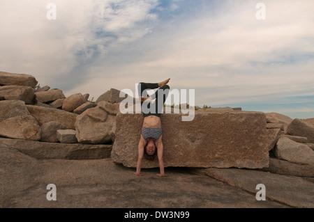 Iyengar Yoga Instructor Demonstrates Adho Mukha Vriksasana Padmasana (Inverted). - Stock Photo