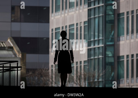 Single silhouette of woman walking through the Broadgate corporate offices development in the City of London. - Stock Photo