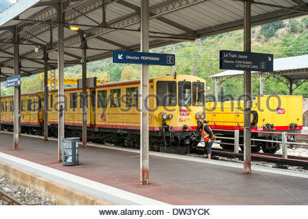A worker inspects the Train Jaune (Yellow Train) at the station in Villefranche-de-Conflent, before departure. - Stock Photo