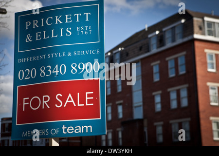 For Sale sign outside a block of purpose built flats. - Stock Photo