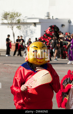 Asian street performer with a golden Buddha mask at a Vietnamese Tet Festival (lunar Festival) in Costa Mesa California - Stock Photo