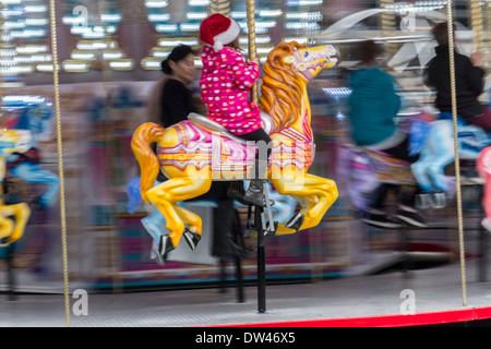 Mother watching daughter ride horse on Merry-go-round - Stock Photo