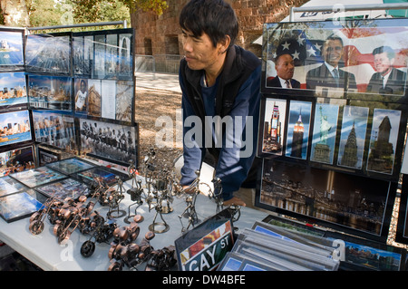A man stands behind a large display of photos, signs and other souvenirs of New York at Battery Park. Vendor selling - Stock Photo