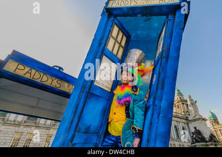 A man dressed in colourful clothes emerges from a 'Tardis' at a St Patrick's day event - Stock Photo