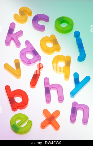 Fridge magnets scattered on a colored background. Lower case letters. - Stock Photo