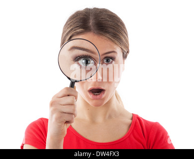 Woman looking through a magnifying glass and being surprised, isolated on white - Stock Photo