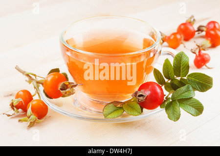 pink herbal tea in glass cup and rose hips fruits - Stock Photo