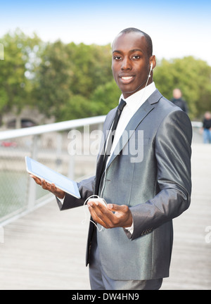 Portrait of a businessman on the phone with hands-free headset and using electronic tablet - Stock Photo