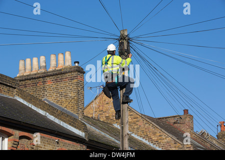 Telecommunications engineer working on an overhead telephone communications pole amongst terraced houses in London, - Stock Photo
