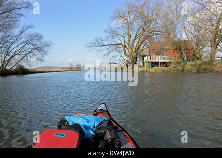 Advanced Elements AdvancedFrame inflatable kayak approaching rustic boathouse beside the River Cam, Cambridgeshire - Stock Photo