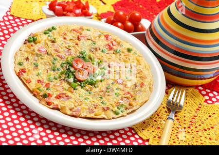 Spanish Tortilla with green peas and tomatoes - Stock Photo