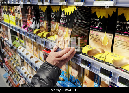 female holding box of hair colouring product in french supermarket - Stock Photo