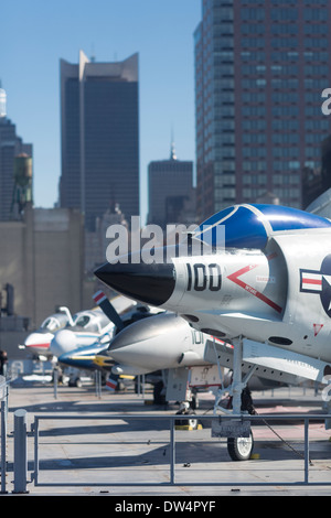 Fighter jets at New York's Intrepid Sea, Air & Space Museum on the flight deck with Manhattan's skyscrapers in background - Stock Photo