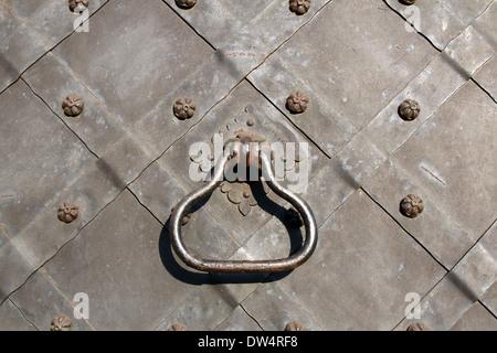 Iron knocker on ancient gate - Stock Photo