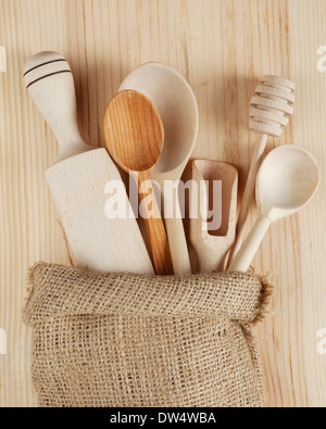 wooden kitchen utensils:spoons, rolling pin, scoop and honey dipper in sack - Stock Photo