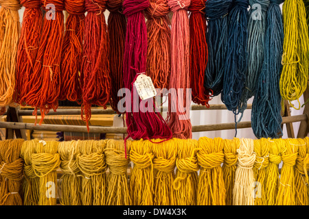 Colourful dyed strands of wool for weaving clothes in spinning mill - Stock Photo