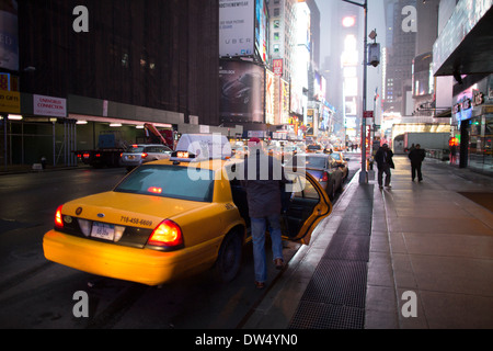 Passenger leaves his yellow cab in Times Square USA - Stock Photo