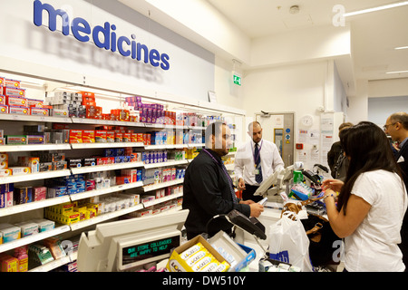A woman buying medicines from the chemist counter, Boots the Chemist,  UK - Stock Photo