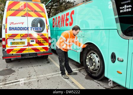 A mobile mechanic / tyre fitter checks a coaches continental tire for tread depth during a regular service & safety - Stock Photo