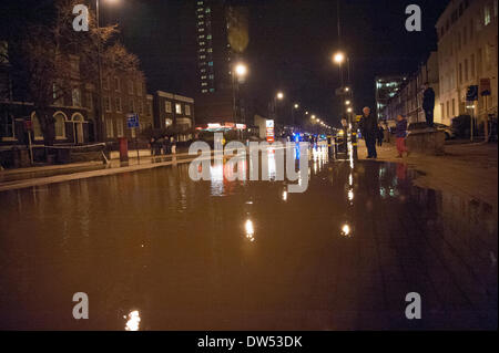 London, UK. 27th Feb, 2014. Flood water covers Clapham Road between the Oval and Stockwell is floodedafter a suspected - Stock Photo
