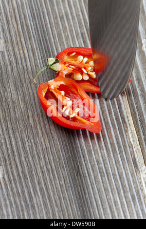 Sliced red hot habanero chili pepper into halves with a kitchen Knife on rustic wooden board - Stock Photo