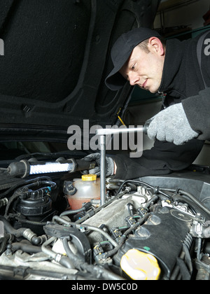 Auto mechanic replacing glow plugs in car diesel engine using spark plug spanner - Stock Photo