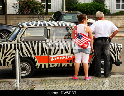 Tourists stand at an East German Trabant car near Checkpoint Charlie in Berlin, August 08, 2013. More and more tourists - Stock Photo