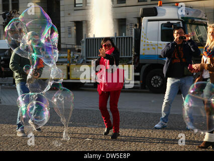 Asian tourists take pictures of giant soap bubbles at the Brandenburg Gate in Berlin, September 29, 2013. More and - Stock Photo
