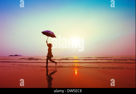 happy woman jumping with umbrella on the beach - Stock Photo