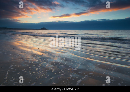 St. Michael's Mount at sunrise from Penzance beach - Stock Photo