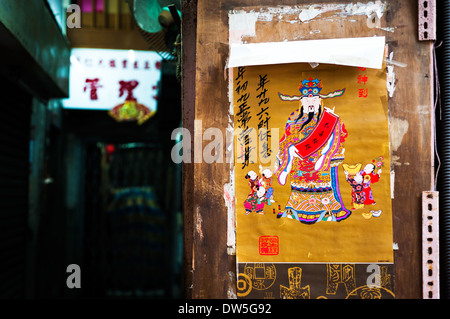 Poster of Chinese money god on wall of residential building, Hong Kong - Stock Photo